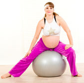 Pregnant female doing pilates exercises on gray ball — Стоковое фото