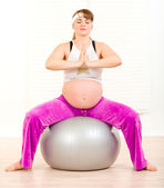 Pregnant female doing pilates exercises on gray ball — Stok fotoğraf