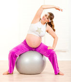 Pregnant female doing pilates exercises on gray ball — Stock Photo