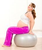 Беременные женщины, делает Пилатес упражнения на серый шар — Стоковое фото