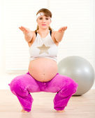 Smiling beautiful pregnant woman doing fitness exercises at living room — Стоковое фото