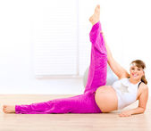 Smiling beautiful pregnant woman doing exercise at living room — Stok fotoğraf