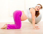 Smiling beautiful pregnant woman making gymnastics at home — Foto Stock