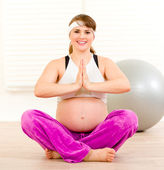 Smiling beautiful pregnant woman doing yoga exercises on floor at home — Stok fotoğraf