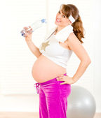 Smiling beautiful pregnant woman in sportswear holding bottle of pure water — Stock fotografie