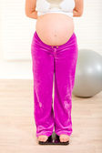 Pregnant female standing on weight scale. Close-up. — Stock Photo