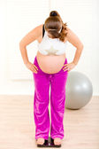 Pregnant woman standing on weight scale at home — Stok fotoğraf