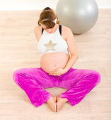 Pregnant woman in sportswear sitting on floor and holding her belly — Photo