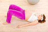 Smiling beautiful pregnant female doing fitness exercises at home — Photo