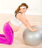 Happy beautiful pregnant woman doing exercises on fitness ball at home — Stock Photo