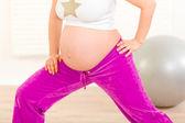 Těhotná žena, která dělá protahovací cvičení doma. detail. — Stock fotografie