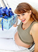 Pregnant female sitting on sofa at home with gifts for her unborn baby — Stock Photo
