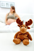 Toy lying on table and pregnant female sitting on sofa in background — Foto Stock