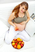 Pregnant female sitting on sofa and holding fruit in hand — 图库照片