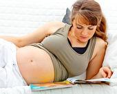 美しい妊娠中の女性雑誌とソファーに横たわって — ストック写真