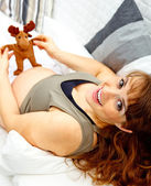 Happy beautiful pregnant woman lying on sofa and holding toy. Close-up. — Stock Photo