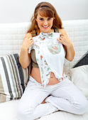 Smiling beautiful pregnant female sitting on sofa at home with baby clothes — Zdjęcie stockowe