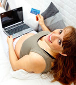 Smiling beautiful pregnant woman on sofa with the laptop and a credit card — 图库照片