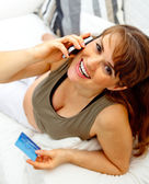 Smiling beautiful pregnant woman with mobile phone and credit card on couch — Zdjęcie stockowe