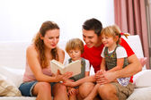 Mother and father reading to twins daughters — Stock Photo