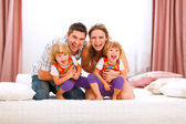 Family portrait of happy mom dad and twins daughters having fun — Stock Photo