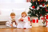 Twee gelukkige tweeling meisje zit met presenteert onder kerstboom — Stockfoto