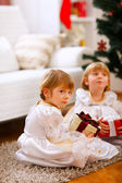 One of twins girl sitting with present with serious expression — Stock Photo