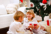 Two twins girl sitting with presents near Christmas tree — Stok fotoğraf