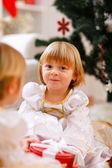 Två glada tvillingar flicka sitter med presenterar nära julgran — Stockfoto