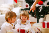 Hand of parent pointing on present to twins girl — Stok fotoğraf