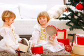 Two smiling twins girl opening presents near Christmas tree — Stock Photo