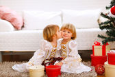Twin girl kissing her sister near Christmas tree with gifts — Stock Photo
