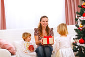 Two twins girl presenting gift to mother near Christmas tree — Stock Photo