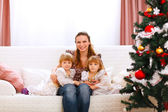 Portrait of mother with two twins daughters near Christmas tree — Стоковое фото
