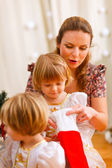 Mother looking with twins daughters inside of Christmas socks — Stock Photo