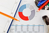Office supplies and financial documents with charts — ストック写真