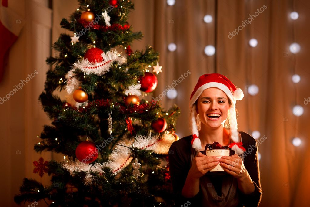 Portrait of smiling young woman near Christmas tree with present box — Stock Photo #8653200