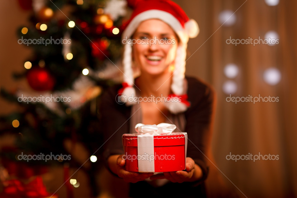 Hand presenting gift box and smiling woman and Christmas tree in background — Stock Photo #8653228