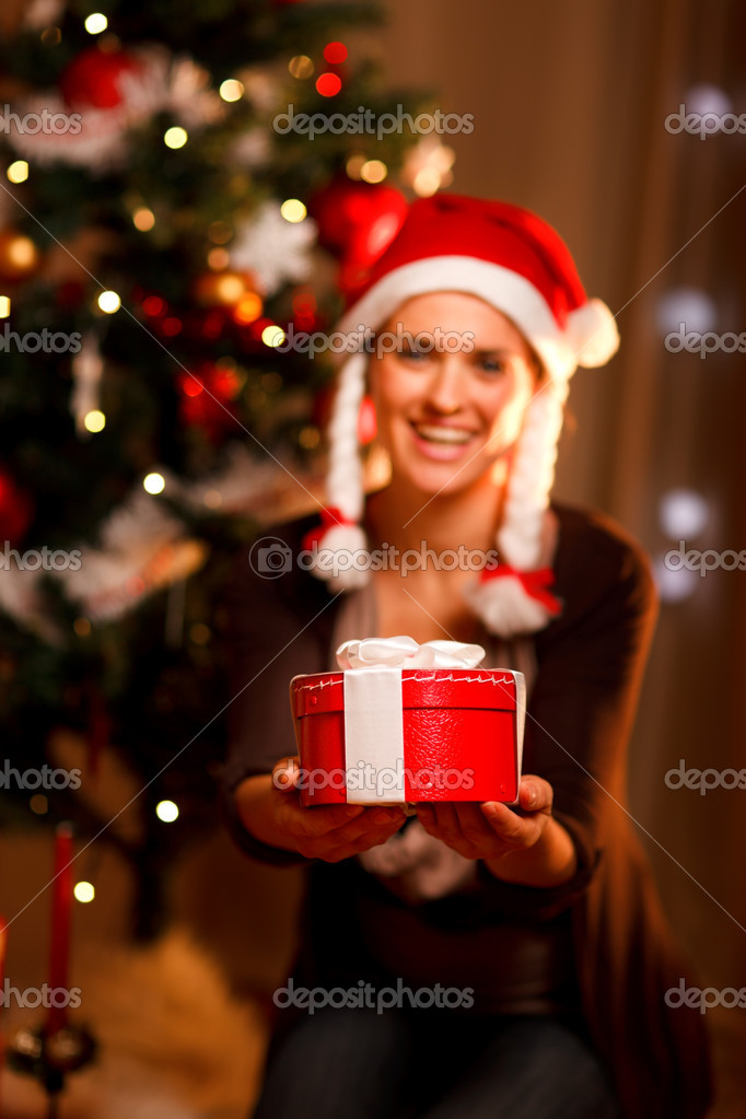 Smiling woman near Christmas tree presenting gift box. Focus on gift — Stock Photo #8653235