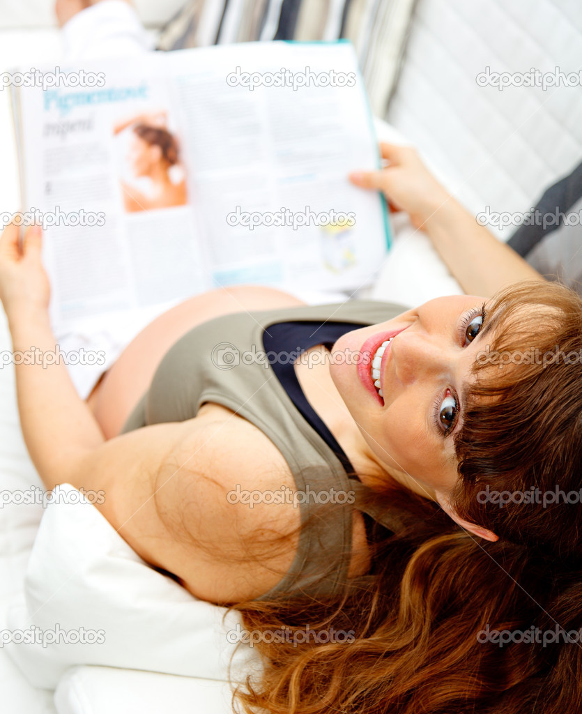 Smiling beautiful pregnant female reading magazine while sitting on sofa at home. — Stock Photo #8656914