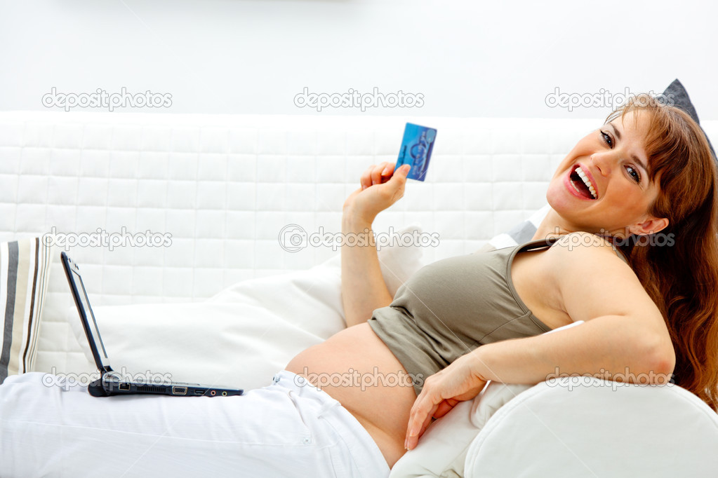 Happy beautiful pregnant woman using credit card to shop from  net — Stock Photo #8657048