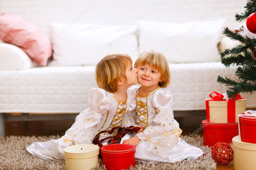 Twin girl kissing her sister near Christmas tree with gifts — Zdjęcie stockowe #8657890