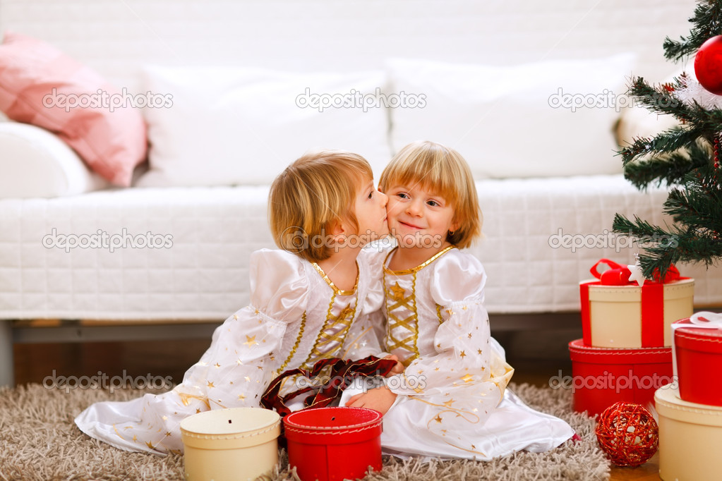 Twin girl kissing her sister near Christmas tree with gifts — Stock fotografie #8657890
