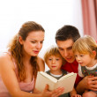 Parents reading to twins daughters — Stock Photo