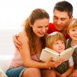 Foto Stock: Happy parents reading to twins daughters