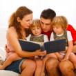 Mother and father looking photo album with twins daughters — Stok fotoğraf