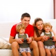 Mother and father playing with twins daughter on console — Stock Photo