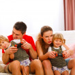Family spending time together and playing on console at home — Stockfoto
