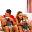 Family spending time together and playing on console at home — Stok fotoğraf
