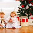 Two twins girl sitting with presents near Christmas tree — Stock fotografie